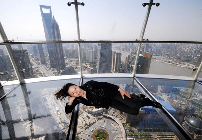 """一位游客躺在上海东方明珠""""悬空观光廊""""玻璃地板上拍照.图片"""